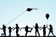 Siluetas de los niños que juegan en el parque Foto de archivo libre de regalías