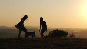 Siluetas de los pares felices que juegan el funcionamiento con su perro lindo durante puesta del sol almacen de metraje de vídeo