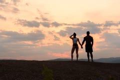 Siluetas de los pares gimnásticos atléticos que miran la salida del sol junta Belleza y perfección del cuerpo humano Fotografía de archivo
