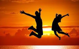 Siluetas de los pares que saltan en puesta del sol Imagen de archivo libre de regalías