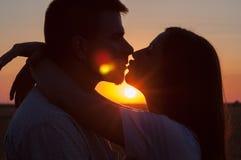 Siluetas de los pares que se besan en la puesta del sol del verano Imagen de archivo