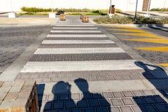 Siluetas de los peatones que se preparan para cruzar el camino cerca del paso de peatones imágenes de archivo libres de regalías
