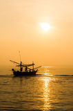 Siluetas de los pescadores que pescan en barco Imagen de archivo