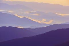 Siluetas de los picos de montaña abajo en la niebla en la noche Foto de archivo libre de regalías