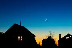 Siluetas de los tejados contra el cielo nocturno con nuevo foto de archivo libre de regalías