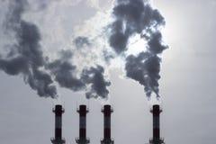 Siluetas de los tubos que emiten el vapor oscuro a la atmósfera contaminación atmosférica por los humos tóxicos Atmósfera en imagenes de archivo