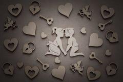 Siluetas de madera de los hombres y de las mujeres, corazones, Amur, castillo, llave Imagenes de archivo