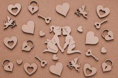 Siluetas de madera de los hombres y de las mujeres, corazones, Amur, castillo, llave Foto de archivo