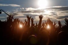 Siluetas de manos en el festival de música del aire libre Foto de archivo libre de regalías