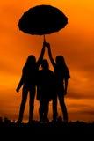 siluetas de muchachas contra el cielo en la puesta del sol, Fotos de archivo