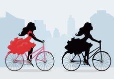 Siluetas de mujeres en la bici Imágenes de archivo libres de regalías