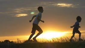 Siluetas de niños corrientes en un campo en la puesta del sol