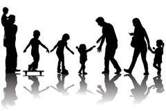 Siluetas de padres con los niños en el parque Imágenes de archivo libres de regalías