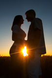 Siluetas de pares jovenes en la puesta del sol Foto de archivo