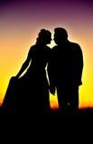 Siluetas de pares jovenes en la puesta del sol Fotografía de archivo