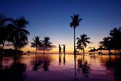 Siluetas de pares jovenes en la puesta del sol escénica fotografía de archivo
