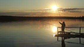 Siluetas de pescadores en la puesta del sol del sol almacen de metraje de vídeo