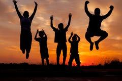 Siluetas de salto de la familia feliz joven en la puesta del sol Foto de archivo libre de regalías