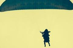 Siluetas de skydivers en un cielo amarillo Fotografía de archivo