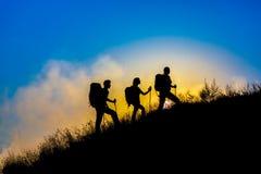 Siluetas de tres personas que caminan con las mochilas Fotos de archivo libres de regalías