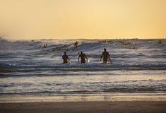 Siluetas de tres personas que practica surf en la puesta del sol en la playa fotos de archivo libres de regalías