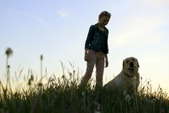 Siluetas de un adolescente que camina con su animal doméstico Imagen de archivo libre de regalías
