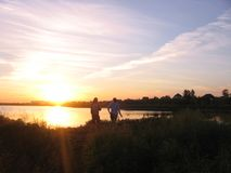 Siluetas de un hombre y de una muchacha en el lago en los rayos del sol poniente fotografía de archivo libre de regalías