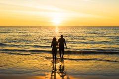 Siluetas de un par joven en la playa imágenes de archivo libres de regalías