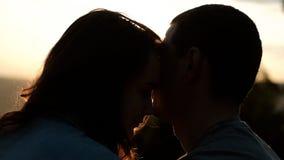 Siluetas de un par joven que abraza suavemente en la puesta del sol almacen de video