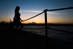 Siluetas de una muchacha que se coloca en un embarcadero cerca del mar contra la perspectiva de una puesta del sol en las montaña Fotos de archivo