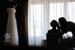 Siluetas de una novia y de un artista de maquillaje foto de archivo libre de regalías