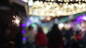 Siluetas Defocused de la gente que disfruta de festival de la calle del invierno para marcar Año Nuevo metrajes
