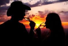 Siluetas del champán de consumición de los pares en la puesta del sol imagen de archivo libre de regalías