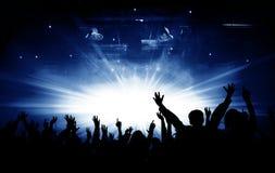 Siluetas del concierto y del fondo brillante de las luces de la etapa Imagen de archivo libre de regalías