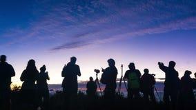 Siluetas del equipo en salida del sol del pico de montaña metrajes