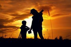 Siluetas del fotógrafo de la madre y del pequeño hijo imágenes de archivo libres de regalías