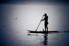 Siluetas del hombre canoeing en agua tranquila Imagenes de archivo