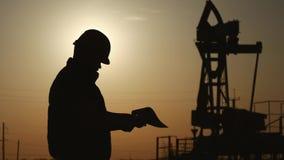 Siluetas del ingeniero en la bomba de la plataforma petrolera de la industria petroquímica en cielo de la puesta del sol El sopor almacen de video