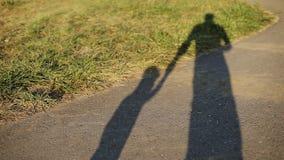 Siluetas del papá y del hijo en el asfalto en verano almacen de video