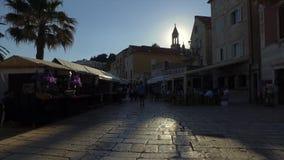 Siluetas del paseo turístico a lo largo de las calles cobbled en la puesta del sol almacen de video