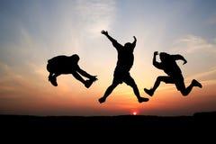 Siluetas del salto de tres hombres Imágenes de archivo libres de regalías