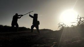 siluetas del samurai dos que lucha con las espadas en los rayos de la puesta del sol Fotografía de archivo