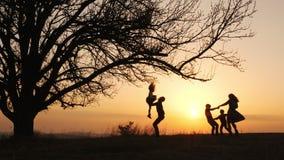 Siluetas del tiempo del gasto de la familia junto en el prado cerca durante puesta del sol metrajes