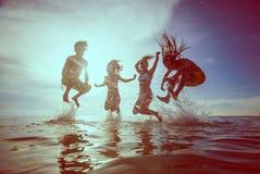 Siluetas del verano de la gente joven feliz que salta en el mar en el b Imágenes de archivo libres de regalías