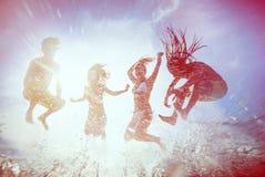 Siluetas del verano de la gente joven feliz que salta en el mar en el b Imagen de archivo libre de regalías