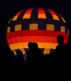 Siluetas delante del globo del aire caliente Fotografía de archivo libre de regalías
