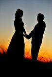 Siluetas en la puesta del sol Imágenes de archivo libres de regalías