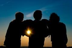 Siluetas en una puesta del sol del horizonte Foto de archivo