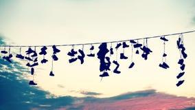 Siluetas estilizadas retras de los zapatos que cuelgan en el cable Imágenes de archivo libres de regalías