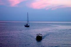 Siluetas flotantes en la puesta del sol fotografía de archivo libre de regalías